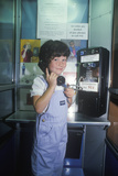 A Girl Using a Pay Telephone Photographic Print