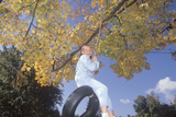 A Girl on a Tire Swing in Autumn, New England Photographic Print