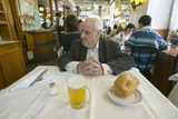 100 Year Old Man Sits Down to a Mug of Beer and a Loaf of Bread in a Restaurant in Madrid, Spain Photographic Print