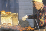 A Senior Citizen Grilling Hot Dogs and Hamburgers Photographic Print