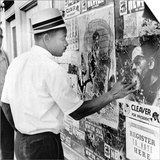 An African American Pokes His Finger into a Bullet Hole in the Oakland Black Panther's Headquarters Poster