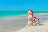 Snowmans Family at Sea Beach in Santa Hat. New Years and Christmas Photographic Print by  EMprize