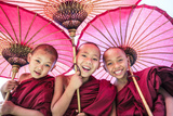 Myanmar, Mandalay Division, Bagan. Portrait of Three Novice Monks under Red Umbrellas (Mr) Papier Photo par Matteo Colombo