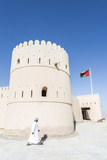 Oman, Sur. Omani Man Walking to the Entrance of Sunaysilah Old Fortress Photographic Print by Matteo Colombo