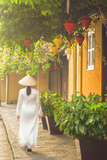 Woman Wearing Ao Dai Dress Walking Along Street, Hoi An, Quang Ham, Vietnam Photographic Print by Ian Trower