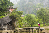 Woman Crossing Bridge with Bicycle to Temple, Tam Coc Nr Ninh Binh, Nr Hanoi, Vietnam Photographic Print by Peter Adams