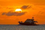 Boat Passing in Front of a Big Glowing Sun During a Spectacular Sunset over the Atlantic Ocean Photographic Print by Mike Theiss