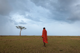 A Masai Man Walking in the Savanna as a Rainstorm Approaches Photographic Print by Sergio Pitamitz