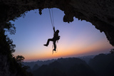 A Climber Descends the Great Arch of Chuanzhang Cave at Sunset Photographic Print by Peter Carsten