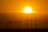 The Sun Sets Behind a Row of Spinning Windmills or Wind Turbines Photographic Print by Mike Theiss