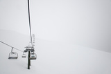 A Chairlift in the Italian Dolomites Disappears into the Mist During a Whiteout Fotografisk tryk af Alex Treadway