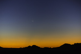 Sunset and the Rising New Moon over Silhouetted Ridges of Desert Mountains Photographic Print by Jonathan Irish