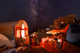 The Milky Way over Candle-Lit Restaurants During a Black-Out Photographic Print by Babak Tafreshi