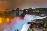 Tourists Enjoying Niagara Falls Illuminated with Colored Lights at Night Photographic Print by Babak Tafreshi