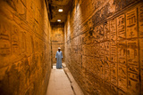 A Man Stands in a Hallway of Medinet Habu Photographic Print by Michael Melford