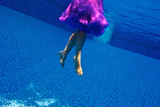 A Model Floats in a Pool, Wearing a Skirt and Heels Photographic Print by Heather Perry