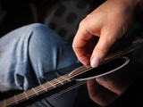 A Man Playing a Carbon Graphite Guitar Made by Rainsong Photographic Print by Amy and Al White and Petteway