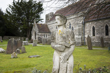 A Lichen Covered Stone Statue in a Graveyard Near a Stone Church in Swanage, England Photographic Print by Jonathan Kingston