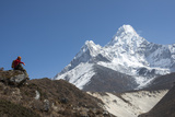 A Hiker Sits Down to Admire Ama Dablam in the Everest Region of Nepal Photographic Print by Alex Treadway