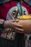 A Quechua Woman Chinchero Style Dress, Carries a Ceramic Bowl of Traditional Stew Photographic Print by Beth Wald