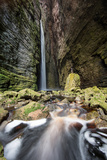 A Man Stands under Cachoeira Fumacinha Waterfall in Chapada Diamantina National Park Photographic Print by Alex Saberi