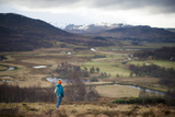 A Woman Walking in the Cairngorms National Park in Scotland Stops to Admire the View Photographic Print by Alex Treadway