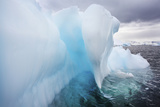 Close Up of a Blue Iceberg under a Stormy Gray Sky Photographic Print by Ira Meyer