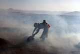 A Tibetan Woman Burning Animal Dung in Her Fields Photographic Print by Sean Gallagher