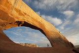 A Young Girl Running in a Sandstone Arch Photographic Print by Peter Mather