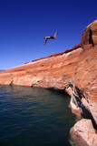 A Cliff Diver Jumping Off a Cliff into a Lake Photographic Print by Keith Ladzinski