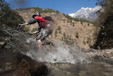 A Mountain Biker Blasts Through a Stream in the Mountains of Nepal Reproduction photographique par Alex Treadway