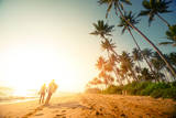 Couple Walking on the Sandy Beach with Palm Trees Prints by Dudarev Mikhail
