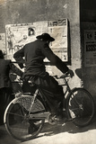 A Priest on a Bicycle Reading Wall Newspapers of the Popular Democratic Front Photographic Print by Luigi Leoni
