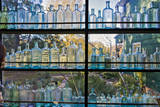 Vintage Blue Glass Bottles Against a Window Wall Decal by Henri Silberman