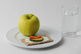 A Green Apple and a Snack on a Plate Next to a Glass of Water Posters