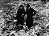 Two Elderly Women Stand Amid the Ruins of the Almshouse That Had Been their Home Poster