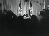 President Harry Truman Seated at His Desk with Lights on and Cameras Rolling Photo