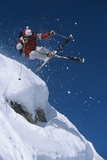 Skier in Mid-Air Above Snow on Ski Slopes Photo