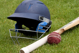 Cricket Ball, Bat and Helmet on Green Grass of Cricket Pitch Fotografisk trykk av Melinda Nagy