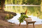 Finnish Summer Landscape and Sauna Objects on Bench by Lake. Photographic Print by  lainea