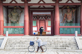 Woman Pushing Bicycle Past Shitenno-Ji Temple, Tennoji, Osaka, Kansai, Japan Photographic Print by Ian Trower