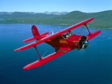 Beechcraft Model 17 Staggerwing Flying over Lake Tahoe, Nevada Photographic Print by Stocktrek Images