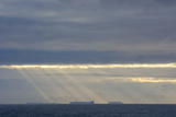 Antarctica. Crepuscular Rays Shining Down onto Tabular Icebergs Photographic Print by Inger Hogstrom