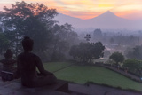 Borobudur, Java, Indonesia. Buddha Statue and Mount Merapi at Sunrise Photographic Print by Charles Cecil