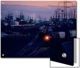 Trains Surrounded by Industrial Plants Print by Kenneth Garrett