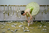 A Ballerina Ties a Pointe Shoe Surrounded by Those She Used in Her Career Photographic Print by Kike Calvo