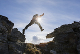 Backlit View of Hiker Leaping Between Rocks Near Noatak River in the Brooks Range Photographic Print by  Design Pics Inc