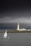 Sailboat Near a Shore with a Lighthouse; Eilean Musdile in the Firth of Lorn,Scotland Photographic Print by  Design Pics Inc