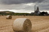 A Cement Production Plant with Hay Bales in a Field in the Foreground; Lothian Scotland Photographic Print by  Design Pics Inc