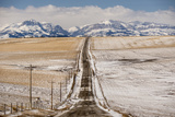A Road Leads Toward the Front Range of the Rocky Mountains in Montana Photographic Print by Michael Melford
